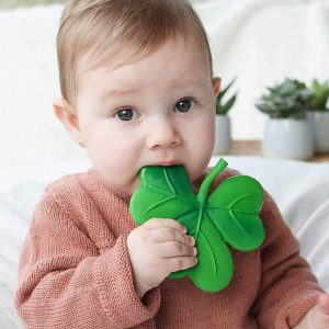 Baby chewing on natural rubber teething toy in the shape of a clover leaf.